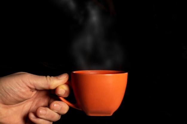 Hand holding mug with steam close up