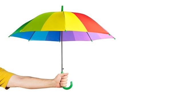 白い背景で隔離の色とりどりの傘を持っている手