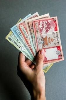 Рука, держащая непальскую валюту (банкноты).
