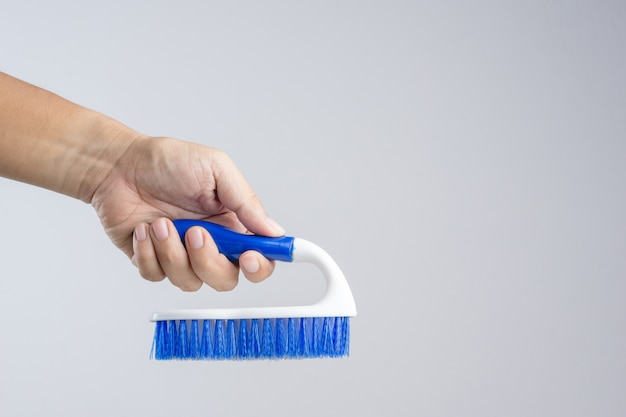 Hand holding new blue floor brush with plastic handle