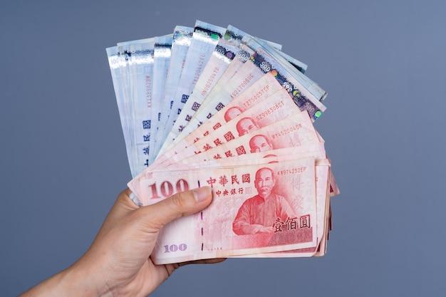 Рука держит новую тайваньскую банкноту