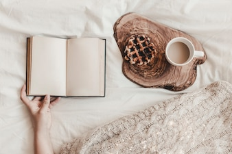 Hand holding notebook near cookie and hot drink on wooden stand