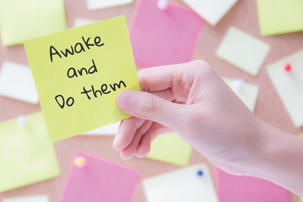 Hand holding a notepaper or post it with words / awake and do them. motivational concept