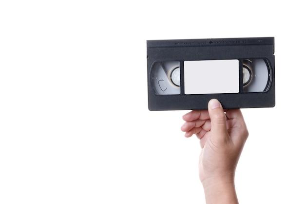 Hand holding old analog vhs video cassette tape