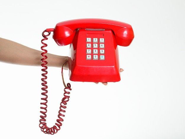 Hand holding old telephone against white wall