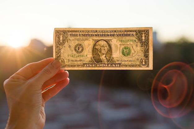 Hand holding one dollar on sun.