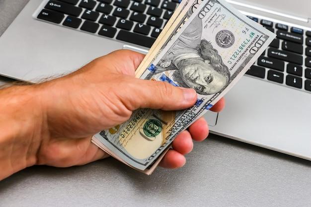 Рука сто пятьдесят долларовых банкнот, клавиатура ноутбука в фоновом режиме.
