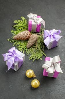 Рука держит один из красочных подарков и украшений на темном фоне