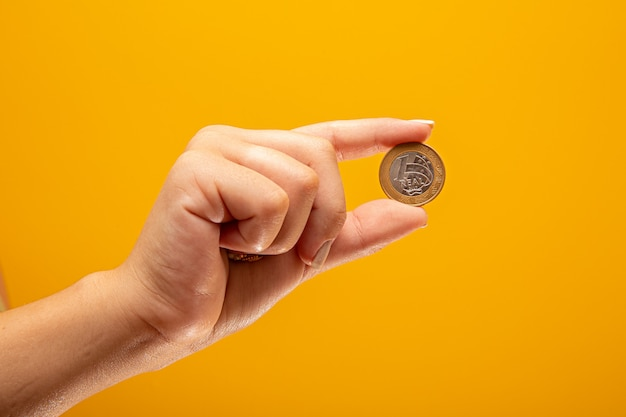 Hand holding one real coin of brazil finance concept.