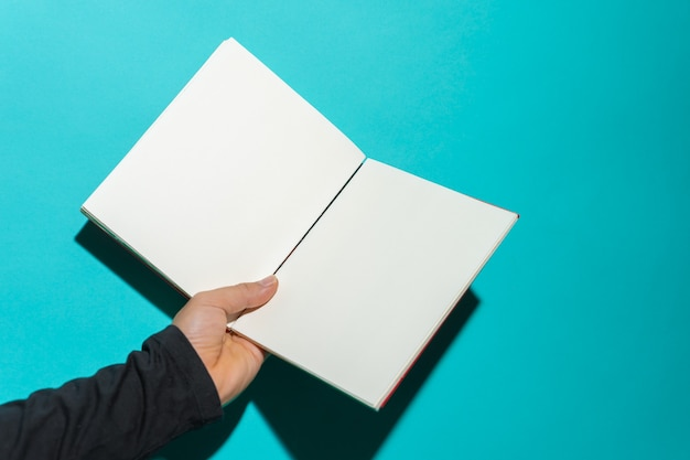 Hand holding open book with clean white pages in front of blue background with copy space for text