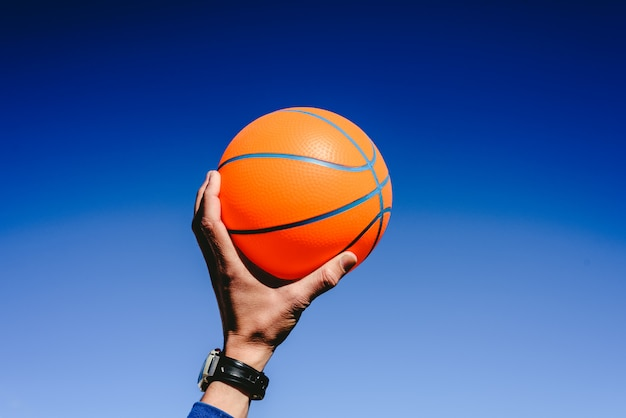 Hand holding an orange basketball ball on blue sky background, invitation to play