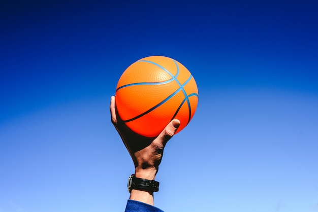 Hand holding an orange basketball ball on blue sky, invitation to play, copy space free area.