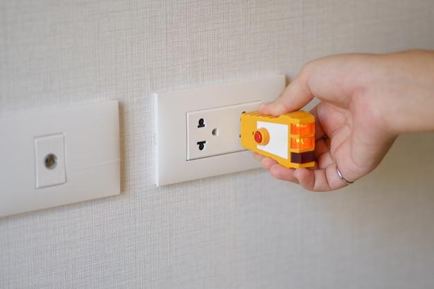 Hand holding orange electric tester