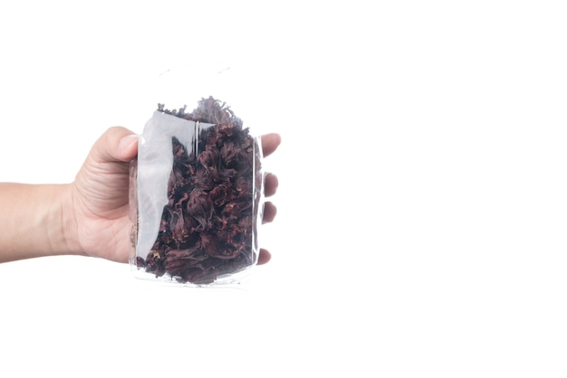 Hand holding pack of dried red roselles for making a herbal tea