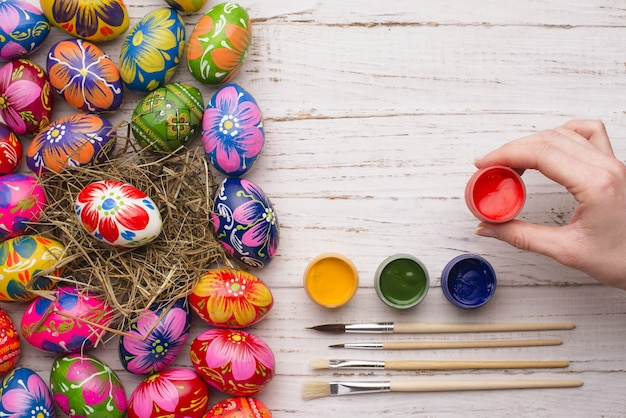 Hand holding a paint jar next to easter eggs