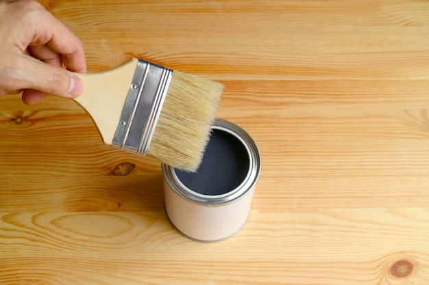 Hand holding paintbrush reaching the opened paint can on wooden plank with free space for design
