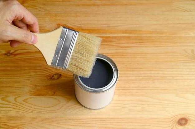 Рука, держащая кисть, достает открытую банку с краской на деревянной доске со свободным пространством для дизайна