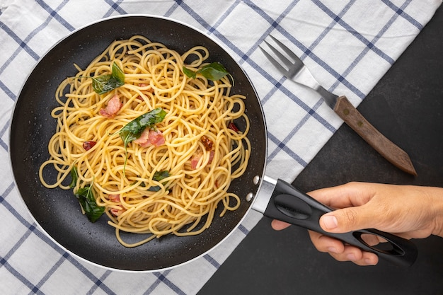 Hand holding pan of spaghetti pasta with dried chilli, garlic, sweet basil and bacon beside fork and napkin on dark tone texture background, top view