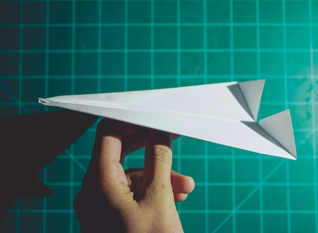 Hand holding a paper airplane engineering background