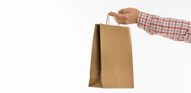 Рука, держащая бумажный пакет