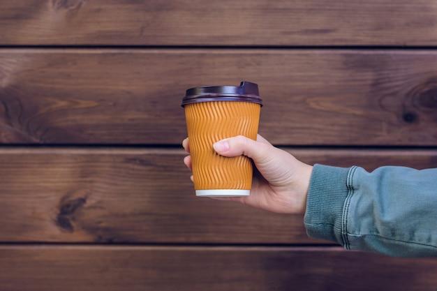 紙コップ茶色の木製の背景を持っている手