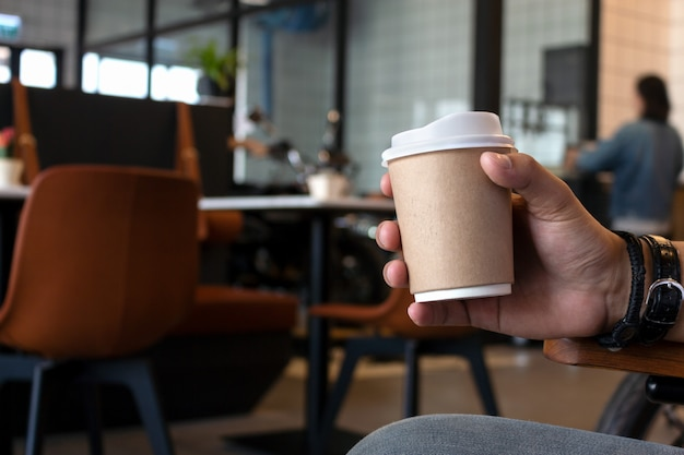 Hand holding paper cup of coffee in cafe