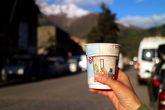 Hand holding a paper cup of coffee with blurry countryside