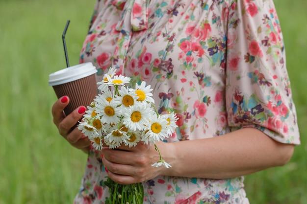 自然な草の背景にコーヒーの紙コップを持っている手