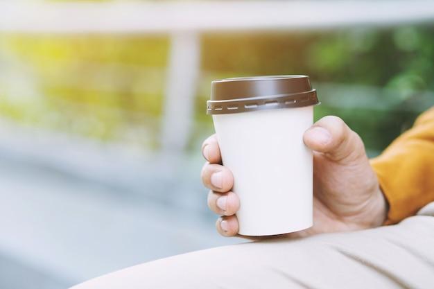 自然な朝の日光の下でコーヒーを飲みながら持ち帰りの紙コップを持っている手。あなたのロゴのためのスペースの場所。テキストを書くためのスペースを残します。