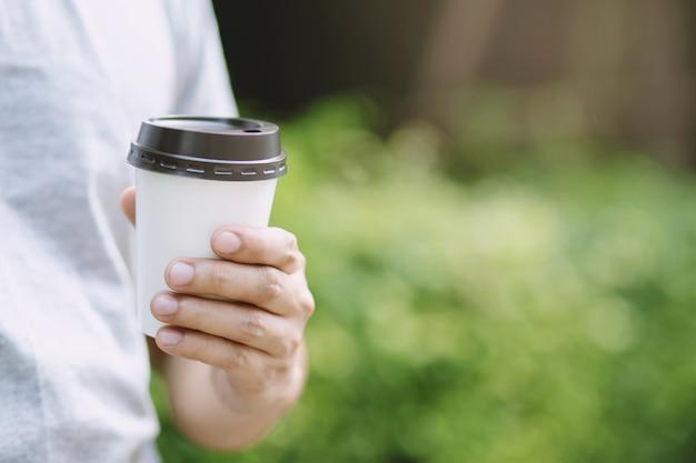 Рука держит бумажный стаканчик на вынос, пить кофе на естественном утреннем солнечном свете