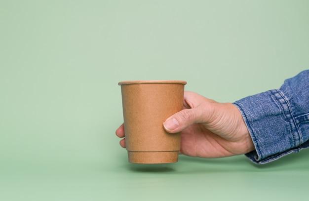 복사 공간이 있는 종이컵을 들고 있는 손. 재활용 및 저장 세계 개념