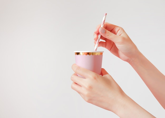 Hand holding paper cup with straws on background.