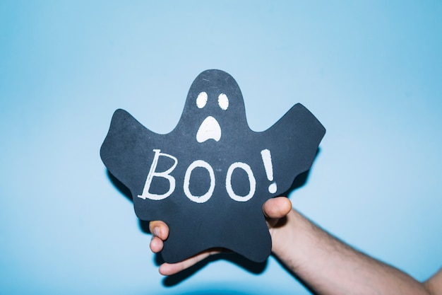 Hand holding paper ghost with boo! inscription