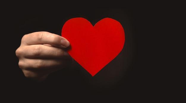 Рука держит бумажное сердце на черном фоне. страхование здоровья, день донора органов, благотворительность. всемирный день здоровья, всемирный день психического здоровья, всемирный день сердца, благодарность и все жизни имеют значение фоновое фото