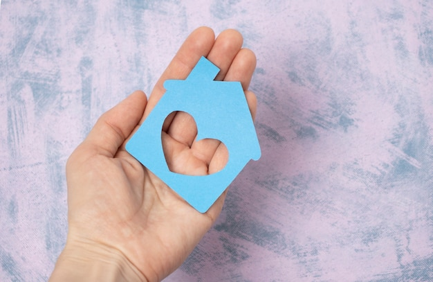 Hand holding paper house, family home, homeless shelter, international day of families, foster home care, family day care, social distancing, stay at home, housing mortgage crisis concept