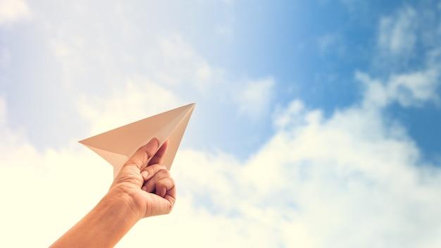 空の背景に紙の飛行機を手に