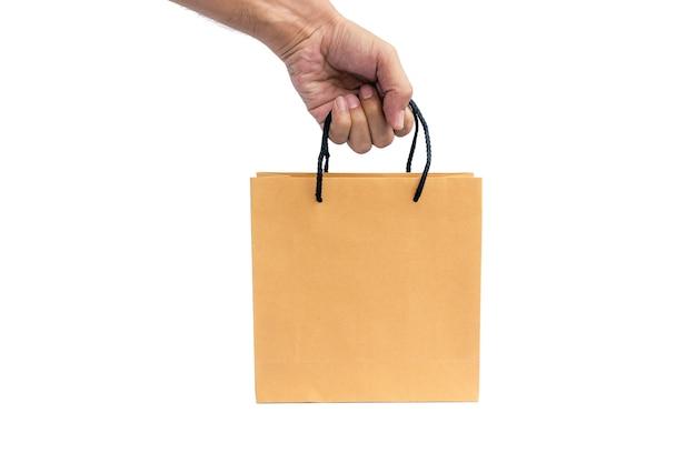 Рука, держащая бумажную хозяйственную сумку изолирована