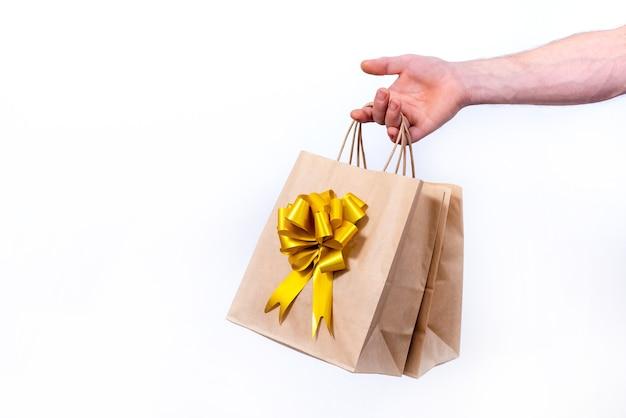 Рука держит бумажные хозяйственные сумки с золотым бантом