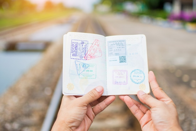 Hand holding passport show immigration stamps on passport with railway background.