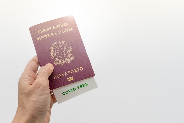 Hand holding passport with green covid free pass on white background