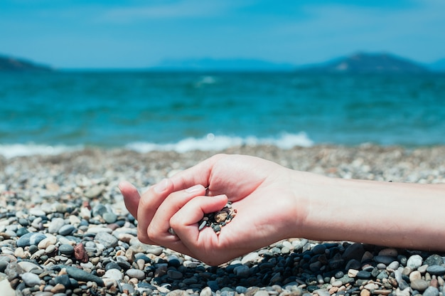 背景にビーチ、ターコイズブルーの海の水で小石を持っている手