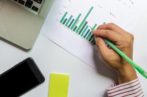 Рука, держащая ручку бизнес-график и диаграмма финансов, бухгалтерского учета, статистики и аналитических исследований с портативным компьютером и смартфоном.