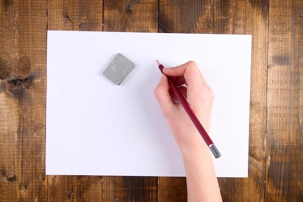 Рука держит карандаш и стирает бумагой на деревянном