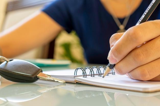 鉛筆を持って、スパイラルノートにメモを取り、テーブルに車のキーを置きます。