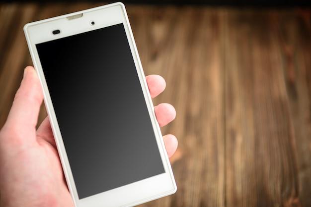 携帯電話の空白の画面を持っている手。木製のテーブルの上のスマートフォン。