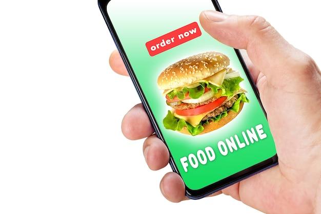 白で隔離される画面上のアプリの注文と配達食品と携帯電話を持っている