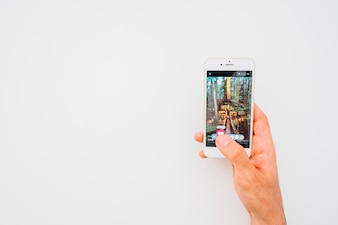 Hand holding phone with facebook photo and copy space