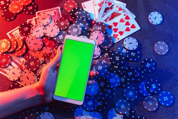 빨간색과 파란색 조명이있는 테이블에 뒷면에 녹색 화면과 포커 게임으로 전화를 들고 손