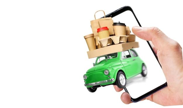 Рука, держащая телефон с ретро-зеленой игрушечной машинкой, доставляющая заказ фаст-фуда
