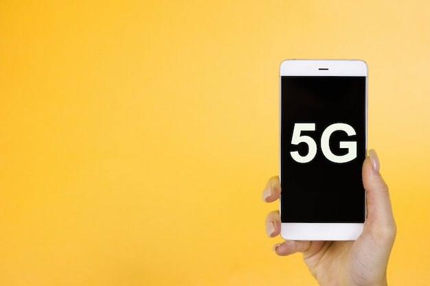 Hand holding phone with a symbol 5g. the concept of 5g network, high-speed mobile internet, new generation networks
